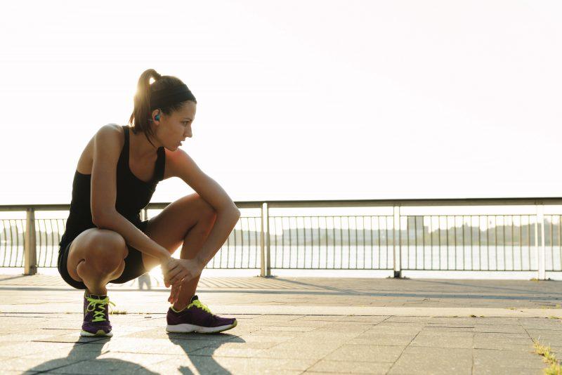 Woman Runner Crouching Wearing BackBeat FIT 2100